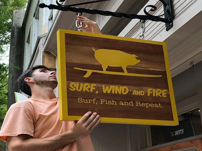 surf-wind-fire-storefront-employee-hanging-sign-new-bern-nc-image